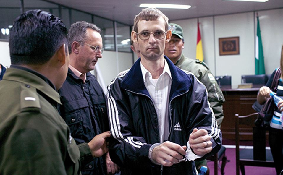 Heinrich Knelsen Kalssen, one of the rapists, is led out of the courtroom by police in Santa Cruz, Bolivia.